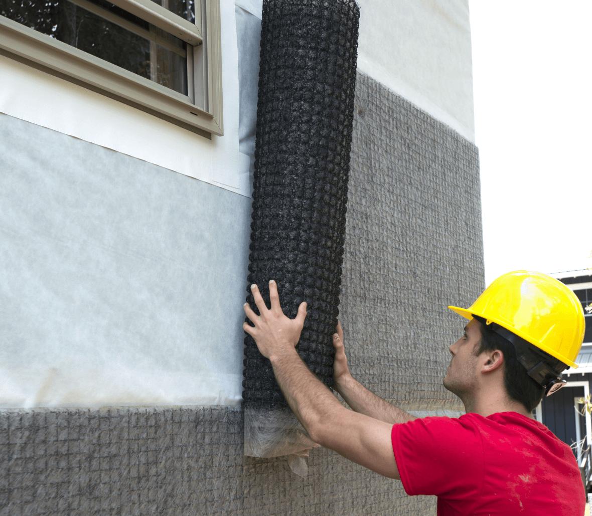 Contractor installing Rainscreen drainage mat EnkaWallDrain on outer wall Credits Enka Solutions_©Low&Bonar